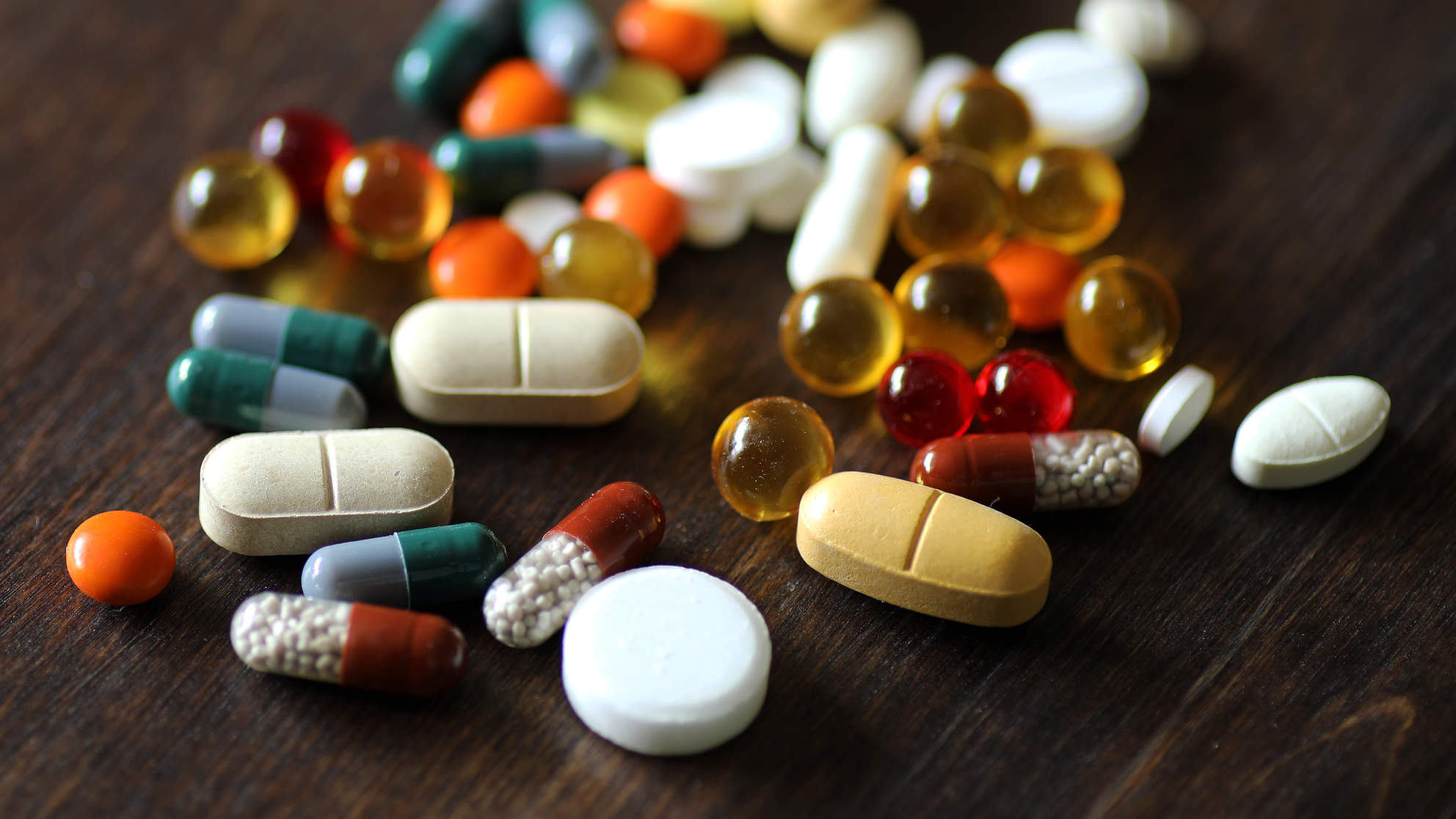Medications and tablets on a wooden texture table
